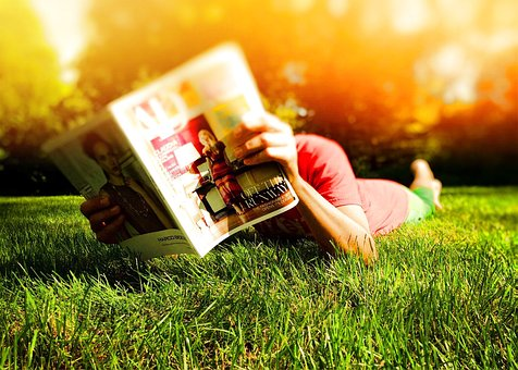 Person lying on their stomach in grass and reading a newspaper.